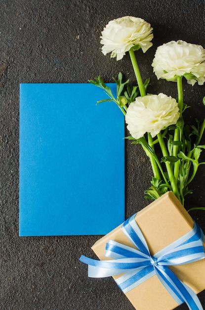 Чистая синяя бумага, подарочная коробка и букет белых цветов Premium Фотографии