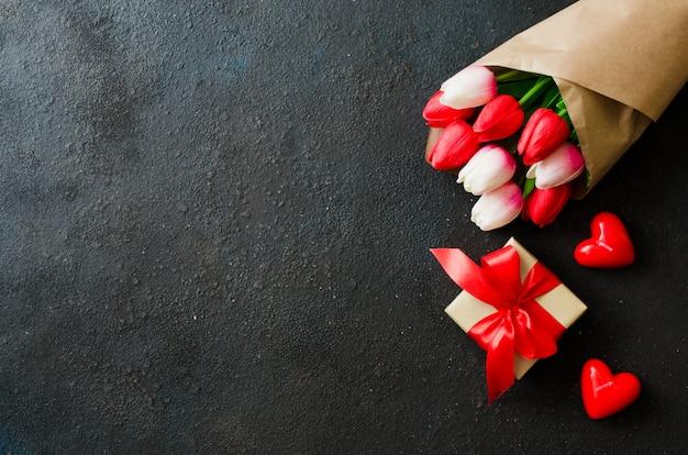 チューリップと暗い背景上のギフトボックスの花束。 Premium写真