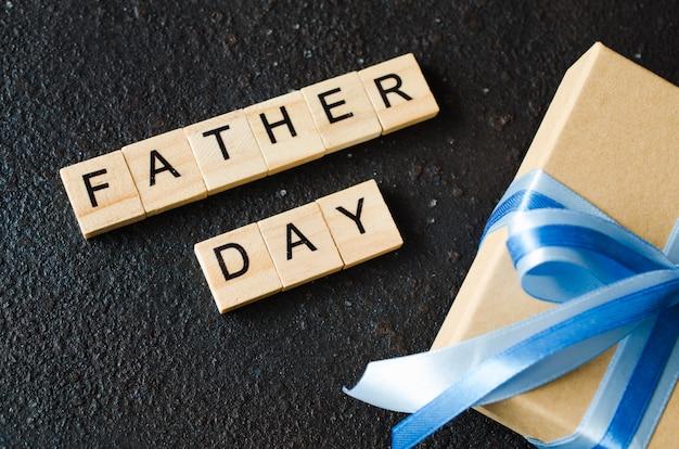 暗い背景に飾られたギフトボックスと幸せな父の日グリーティングカード。 Premium写真