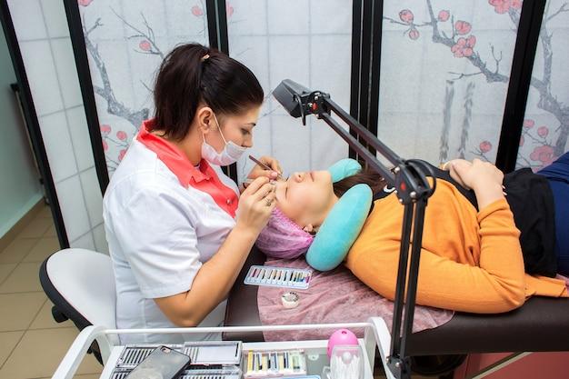 まつげエクステの達人はクライアントと美容院で働きます。少女はスタジオでまつげを増やす Premium写真