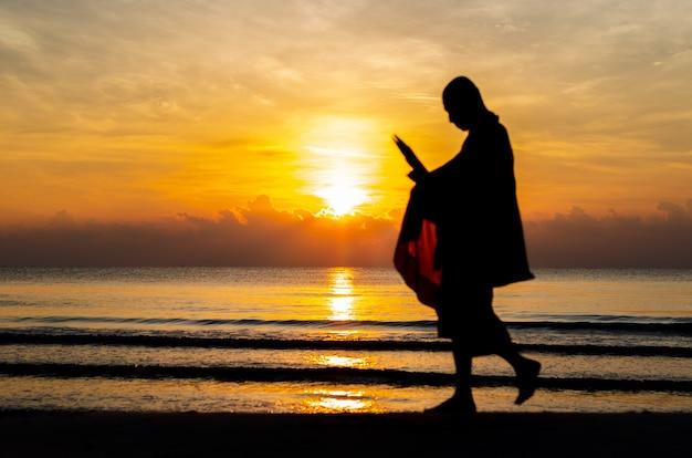 Восход солнца с отражением на море и пляж, которые размыты силуэт фото буддийского монаха. Premium Фотографии
