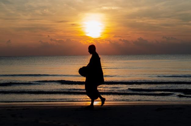 仏教の僧侶のシルエット写真がぼやけている海とビーチでの反射との日の出。 Premium写真