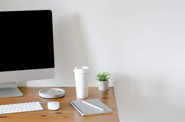 一杯のコーヒーとティランジアの空気植物と木製のテーブルの上の現代のパソコン画面 Premium写真