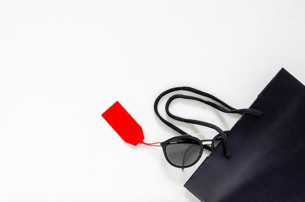 ブラックフライデー販売コンセプトの白い背景に赤い値札とショッピングバッグと黒のサングラスのフラットレイアウト。 Premium写真