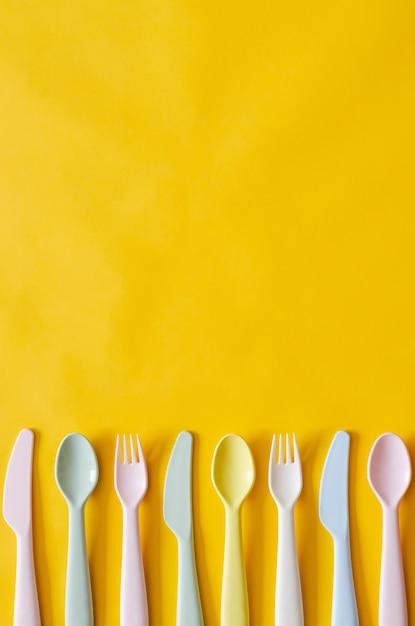 カラフルなフォーク、スプーン、ナイフテキストの空スペースで黄色の背景に。 Premium写真