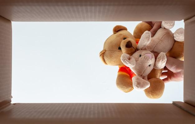 Упаковка кукол в коробку для домашнего переезда. фотография занимает от нижней точки зрения. Premium Фотографии