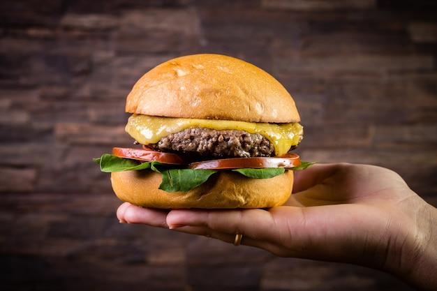 Рука бургер из говядины с сыром, руколой и картофелем фри на деревенском фоне Premium Фотографии