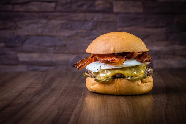 クラフトビーフバーガー、チーズ、卵、ベーコン、ピクルスの木製テーブル Premium写真