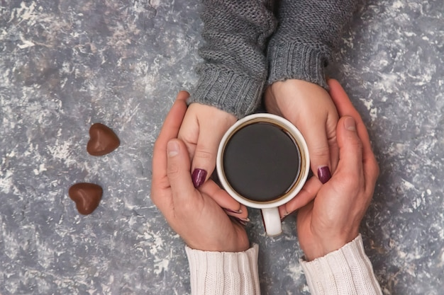 コーヒーのカップを保持している男性と女性の手。セレクティブフォーカス Premium写真