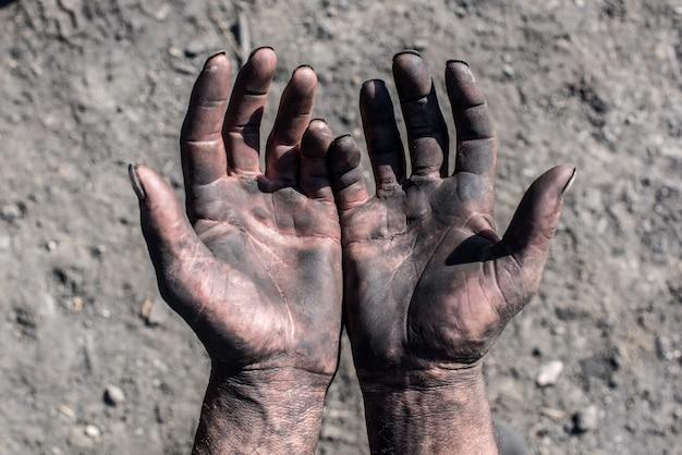 チャコール・バーナー汚れた手を持つ労働者の男。労働者の手。 Premium写真