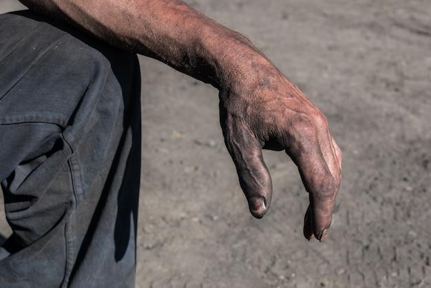 チャコール・バーナー汚れた手を持つ労働者の男。労働者の手。汚れた手を持つ労働者の男。 Premium写真