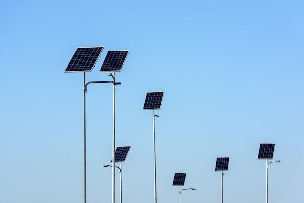 Уличное освещение работает от солнечных панелей на фоне голубого неба. Premium Фотографии