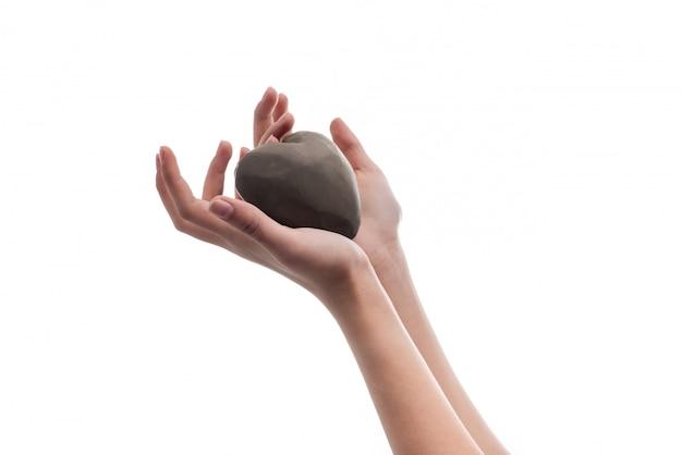 粘土から作られた心を持って女の子の手。愛とバレンタインデーのシンボルです。 Premium写真