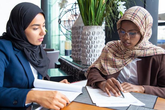 カフェでドキュメントを勉強している深刻な女性の同僚 無料写真