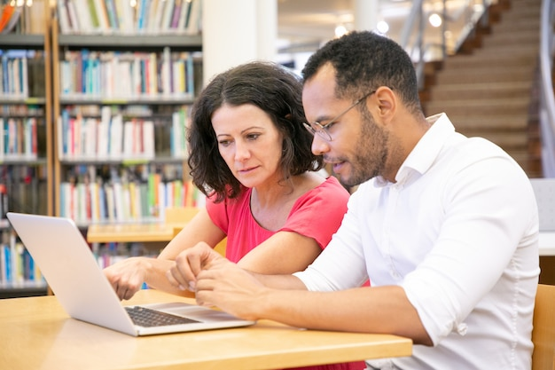 Пара взрослых студентов, которые смотрят контент на компьютере Бесплатные Фотографии