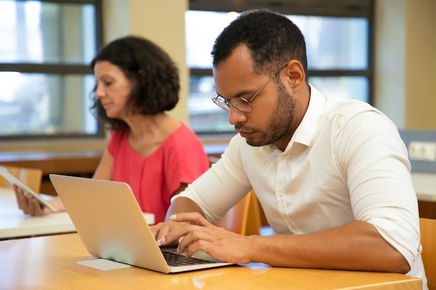 コンピュータークラスで働く深刻な男性ラテン研修生 無料写真