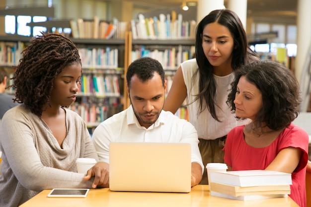 公共図書館でラップトップを扱う深刻な成熟した学生 無料写真