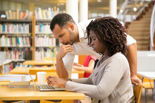 図書館でノートパソコンと一緒に働く思慮深い人々 無料写真