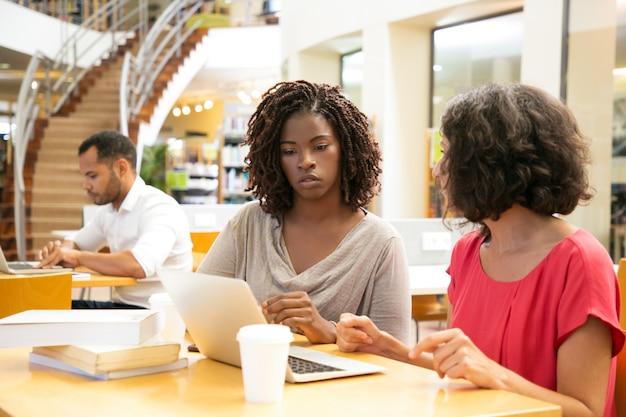図書館でラップトップを使用して思慮深い女性 無料写真