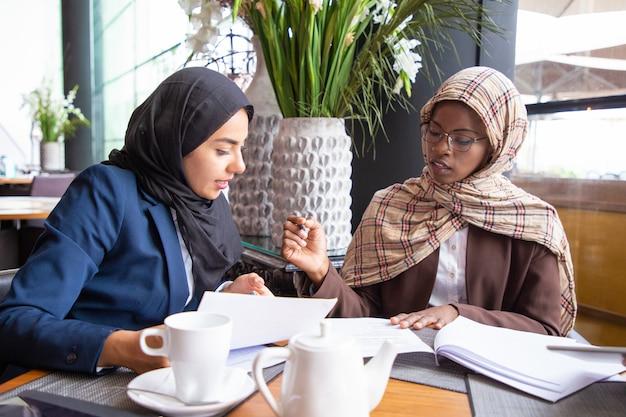 ドキュメントを分析し、議論する女性のビジネス部門の同僚 無料写真