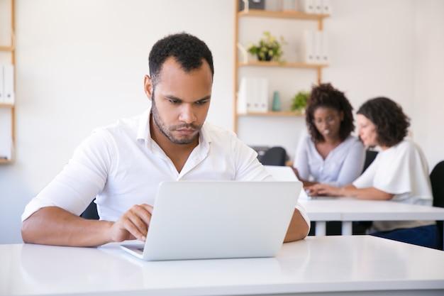 オフィスでラップトップを使用して男性従業員に焦点を当てた 無料写真