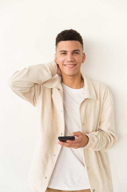 Довольный молодой человек держит мобильный телефон Бесплатные Фотографии