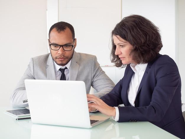 Серьезные коллеги, использующие ноутбук Бесплатные Фотографии
