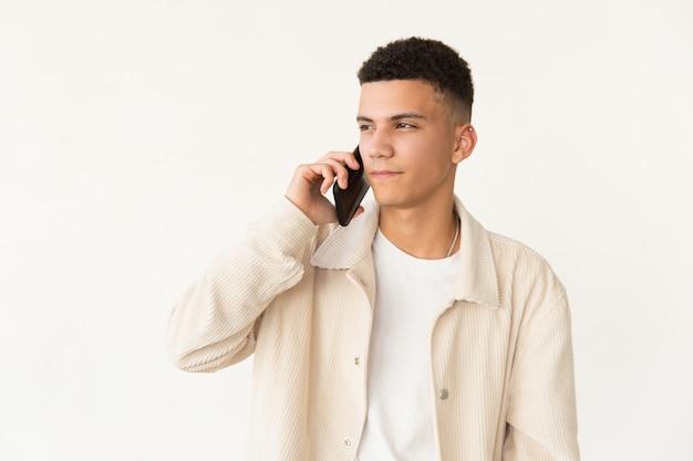 Серьезный молодой человек разговаривает по мобильному телефону Бесплатные Фотографии