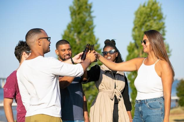 公園でビールパーティーを楽しんで幸せな多民族の友人 無料写真