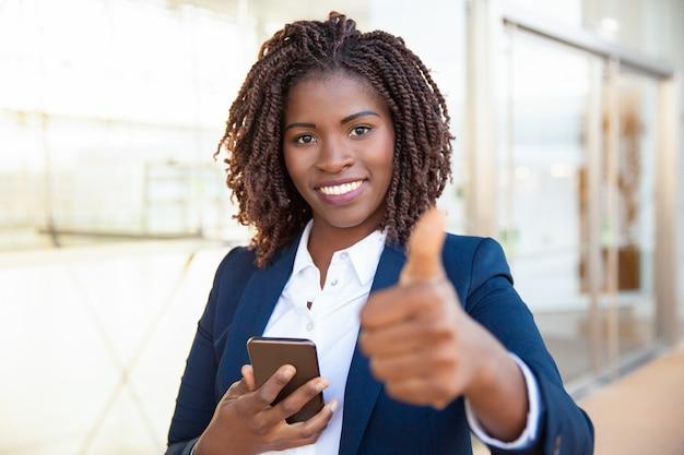 携帯電話を保持している幸せな満足している女性客 無料写真