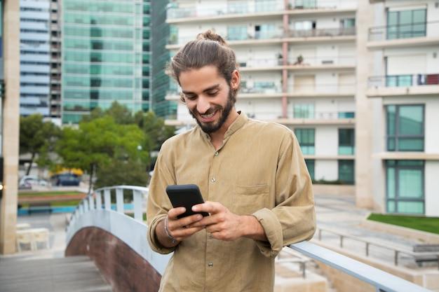 スマートフォンを使用して陽気な若い男 無料写真