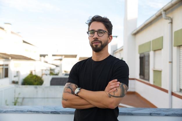 Уверенный стильный парень с татуировками позирует на балконе квартиры Бесплатные Фотографии