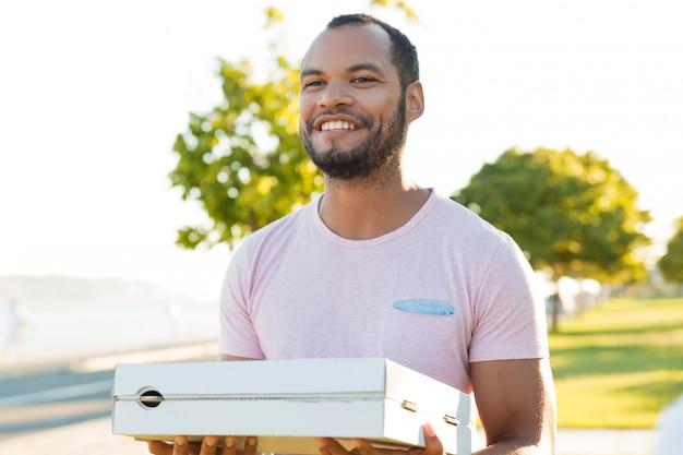ピザを提供するフレンドリーな興奮したハンサムな男 無料写真