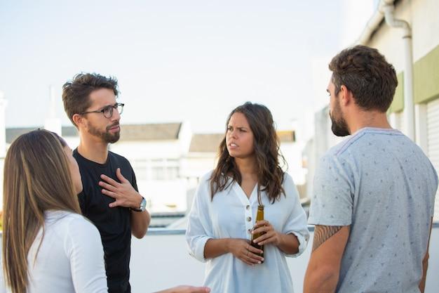 Группа друзей делится новостями за бутылкой пива на открытом воздухе Бесплатные Фотографии