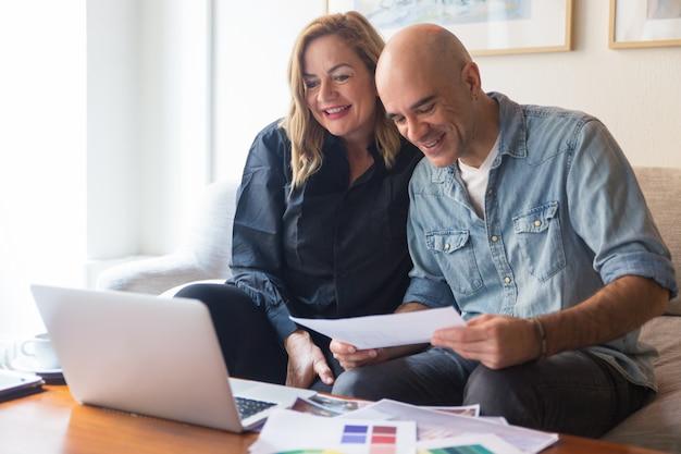 Счастливая пара клиентов разговаривает с дизайнером интерьера Бесплатные Фотографии