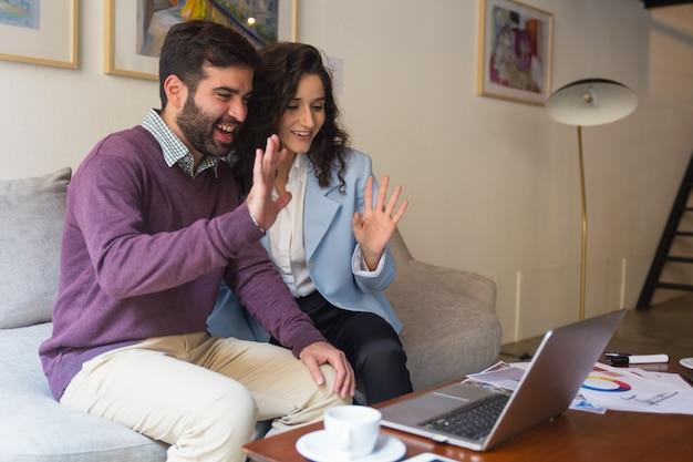 コンピューターの画面でこんにちはを振って幸せなカップル 無料写真