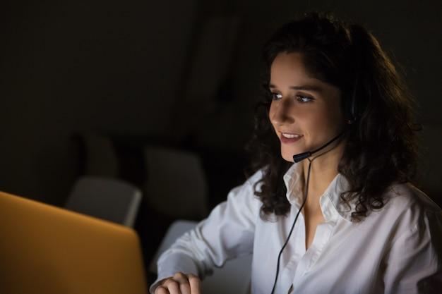 暗いオフィスでヘッドセットを持つ女性の笑みを浮かべてください。 無料写真