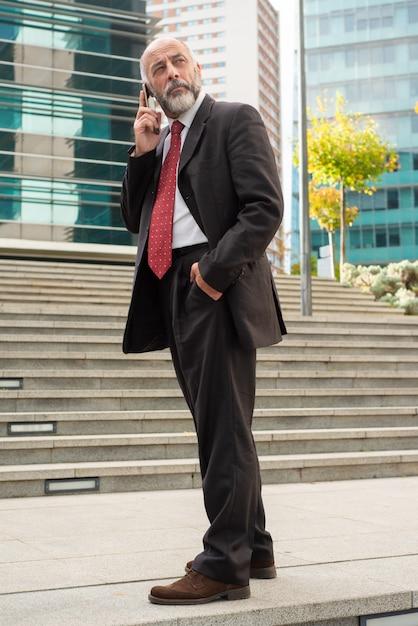 Бизнесмен говорить по мобильному телефону и глядя Бесплатные Фотографии