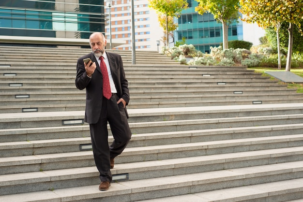 ステップの上を歩くと、スマートフォンを使用するビジネスマン 無料写真