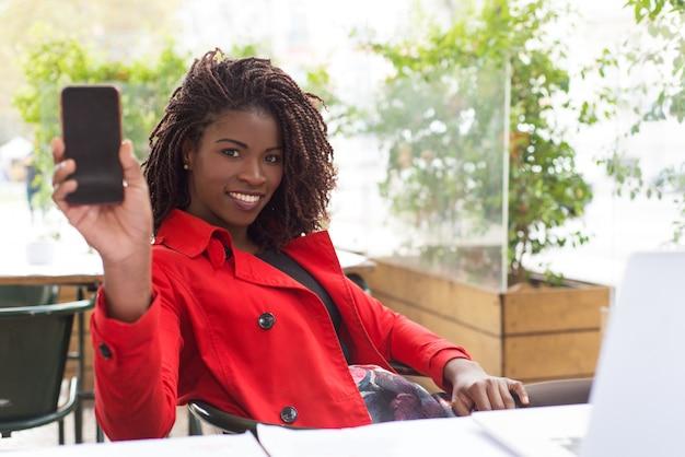 空白の画面を持つスマートフォンを示す陽気な女性 無料写真
