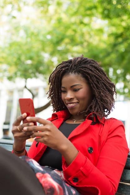 Жизнерадостная женщина, используя смартфон на улице Бесплатные Фотографии