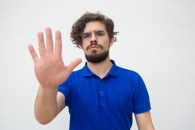 Серьезный строгий парень делает жест рукой стоп Бесплатные Фотографии