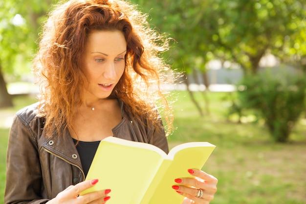 公園に立って、本を読んで興奮して興奮した女性 無料写真