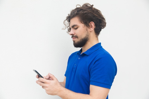 Сторона сфокусированного парня отправляя смс сообщение на смартфоне Бесплатные Фотографии