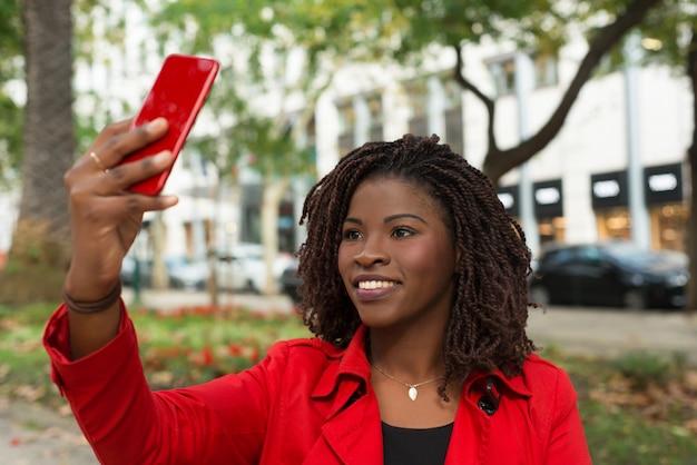 Улыбается женщина, принимая селфи с смартфон на открытом воздухе Бесплатные Фотографии