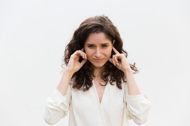 Подчеркнутая раздраженная женщина закрывает уши руками Бесплатные Фотографии
