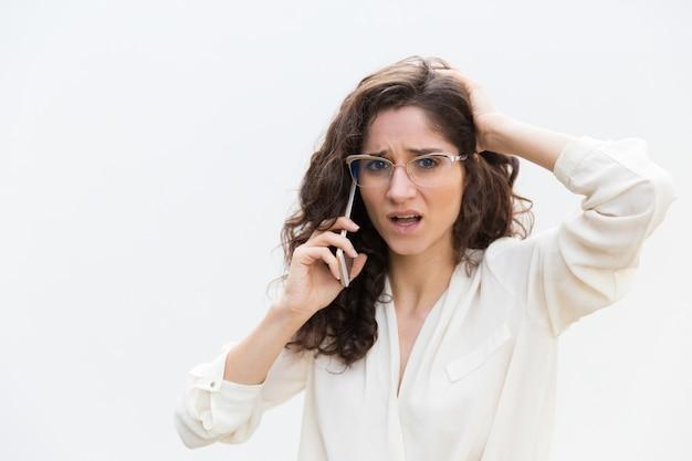 Подчеркнул озадаченная женщина в очках разговаривает по мобильному телефону Бесплатные Фотографии