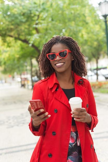 Стильная женщина с смартфон смеется в парке Бесплатные Фотографии