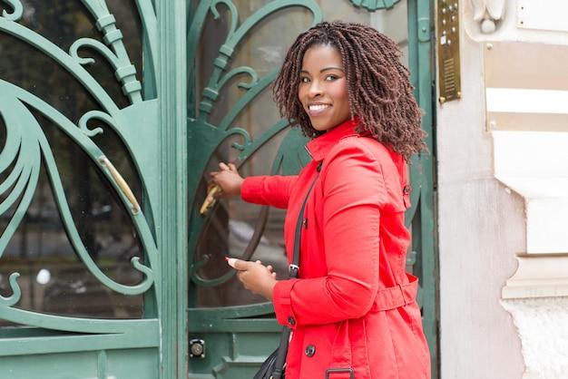 ドアを開けると笑顔の女性 無料写真