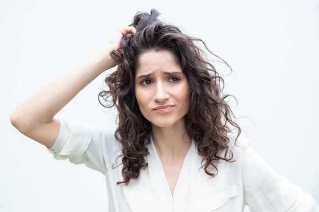 Беспокоит задумчивая женщина, почесывая голову Бесплатные Фотографии